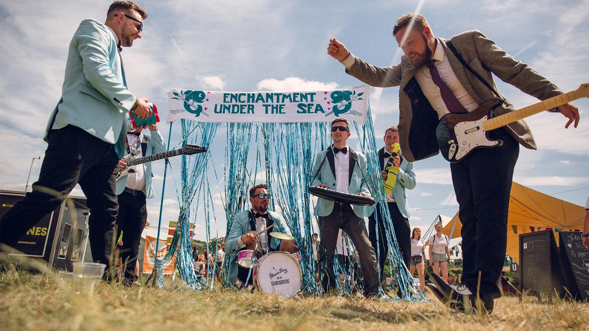 Men in blue jackets and bow ties pretend to play inflatable instruments in a field. Photo by Ben Morse.